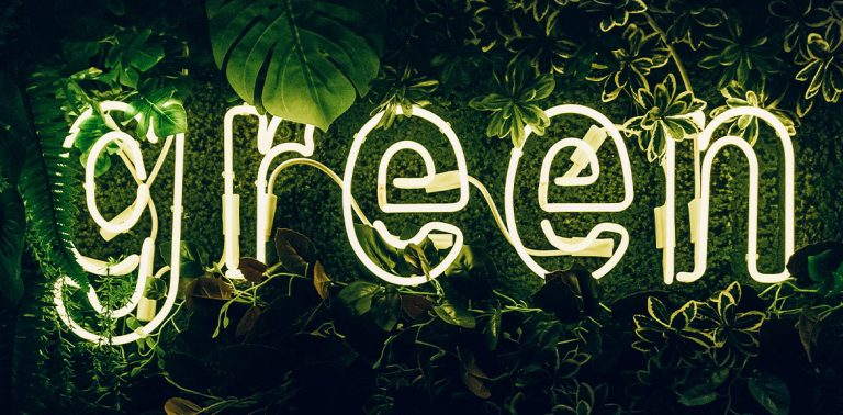 """scritta neon """"green"""" su fondo verde con le piante"""